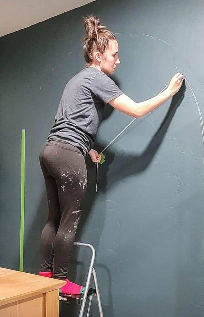a woman holds a string attached to chalk and draws a semicircle on the wall