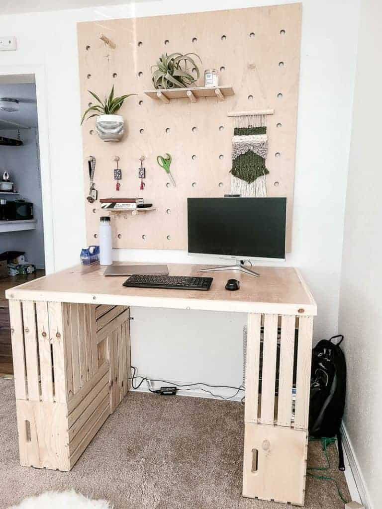 DIY wood crate desk with a computer monitor on it and a wood plywood pegboard wall above it