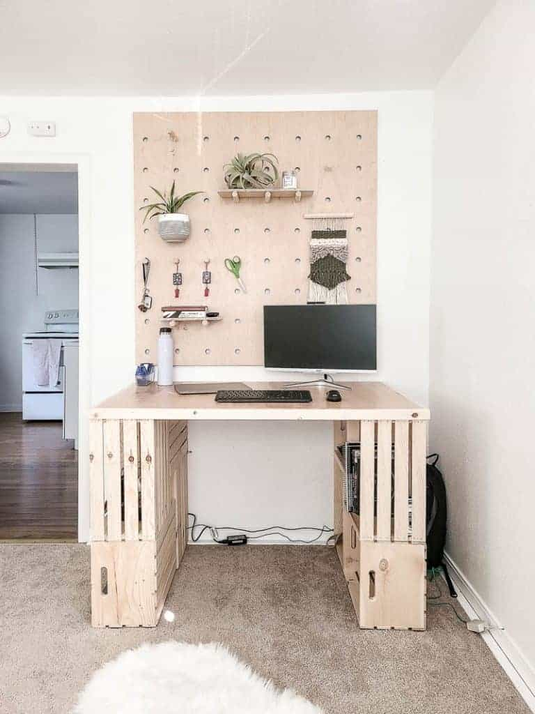 wood crate desk with a computer on it and a wood storage wall behind it