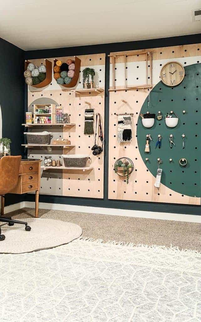 shows the dark teal wall with a wood pegboard with painted shapes with multiple craft supplies