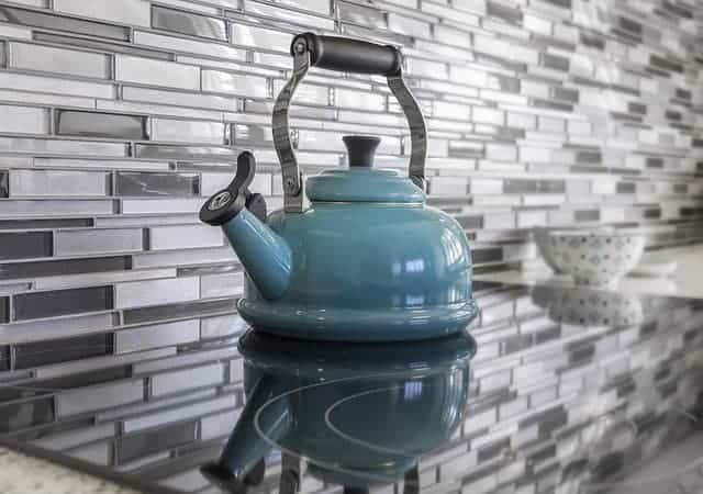 different shades of gray glass tile as a backsplash on a kitchen counter with a blue tea pot