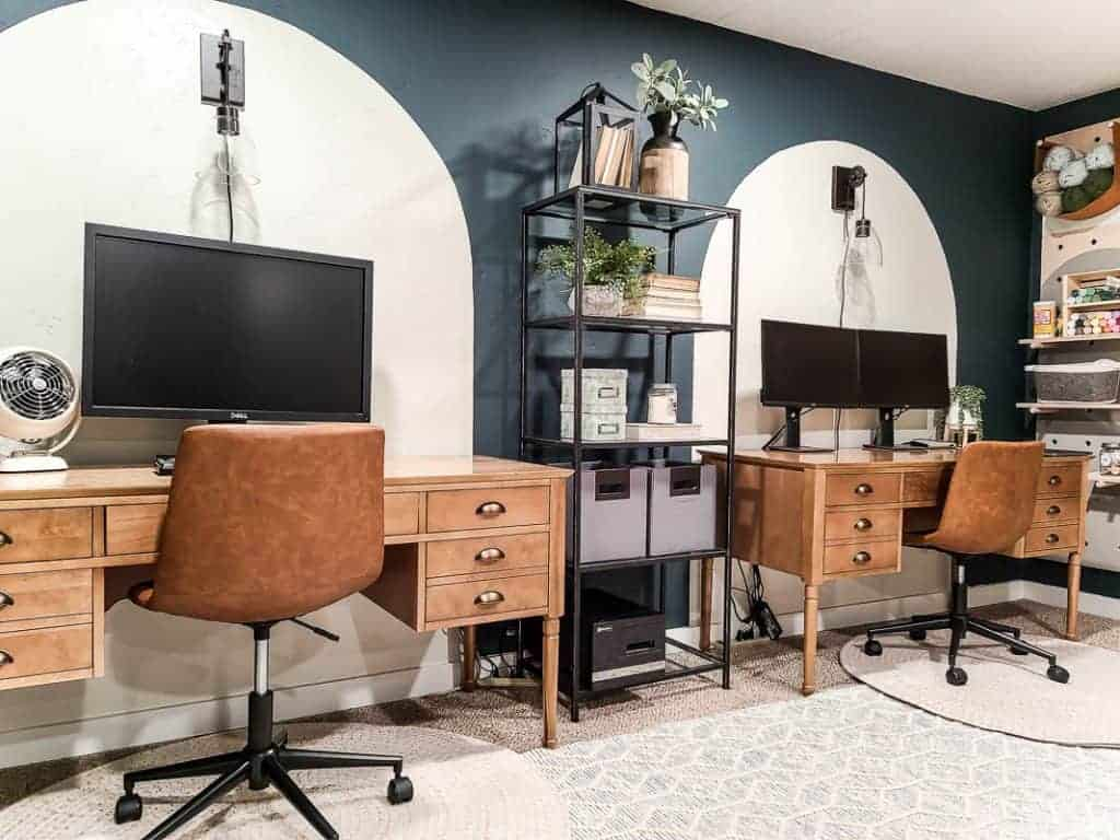 shows his and hers wood desks in a dark teal room with white painted arches and white rugs