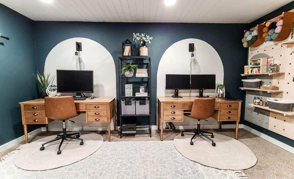 shows a dark green and white office space with two wooden desks, painted arches on wall, boho area rug and leather task chairs and a giant wood pegboard