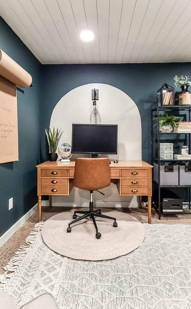 A desk setup is aligned with the painted arch on the wall