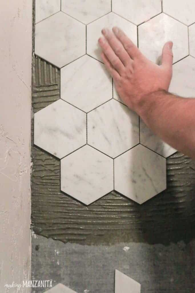 shows a hand pressing white hexagonal marble tile flooring against thinset mortar