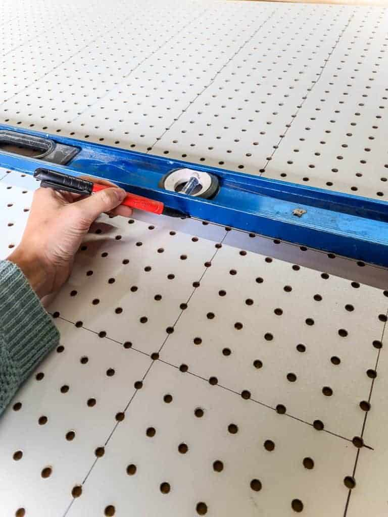 Drawing line on pegboard panel with a sharpie