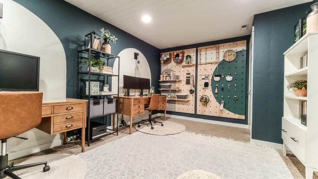 dark painted walls in home office with two wood desks and leather chairs with a giant wood pegboard wall with craft supplies and a white bookcase