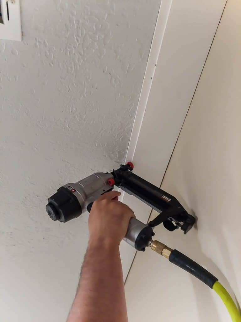 Using a nail gun to nail shiplap planks to ceiling