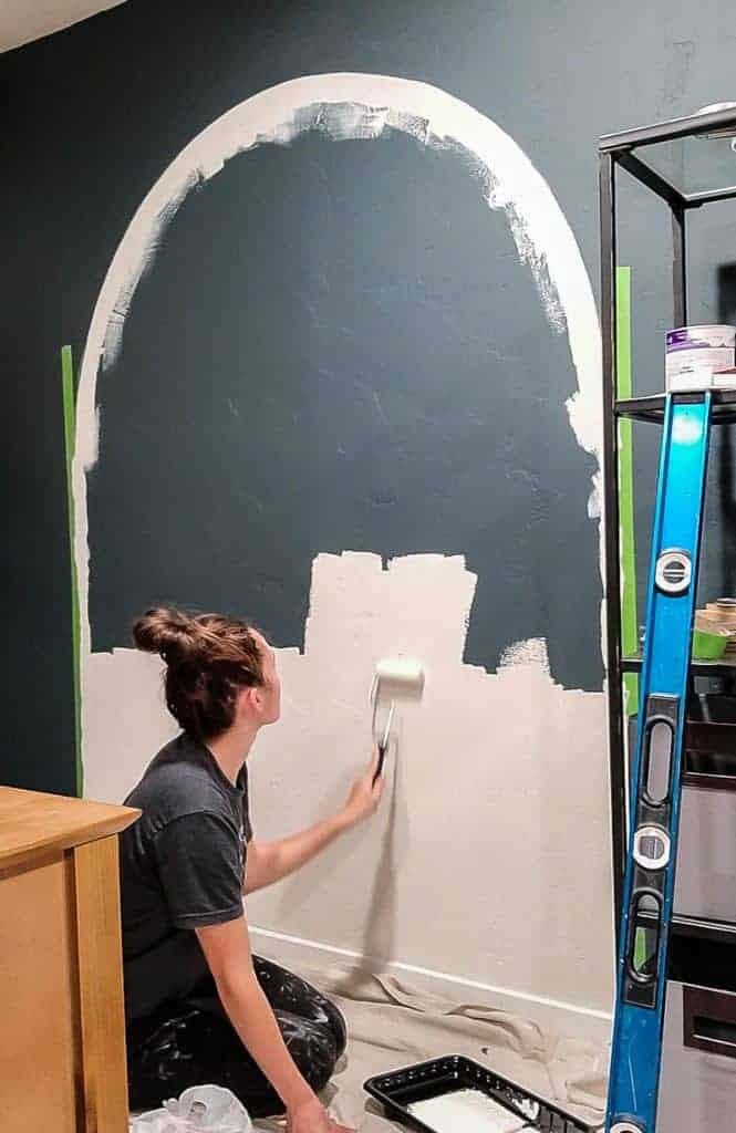 a roller brush is used to paint the inside of a painted arch on the wall