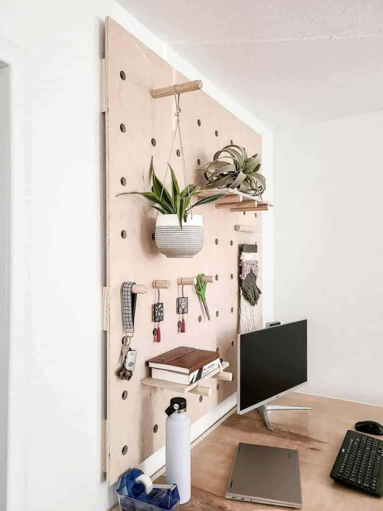shows the top side of the wood crate desk with plants and other stuff hanging from a wood peg wall and has a computer on the desk