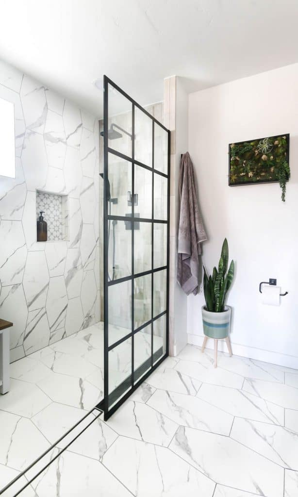 shows a modern boho bathroom with white hexagonal marble tile in the bathroom with black framed window shower panels