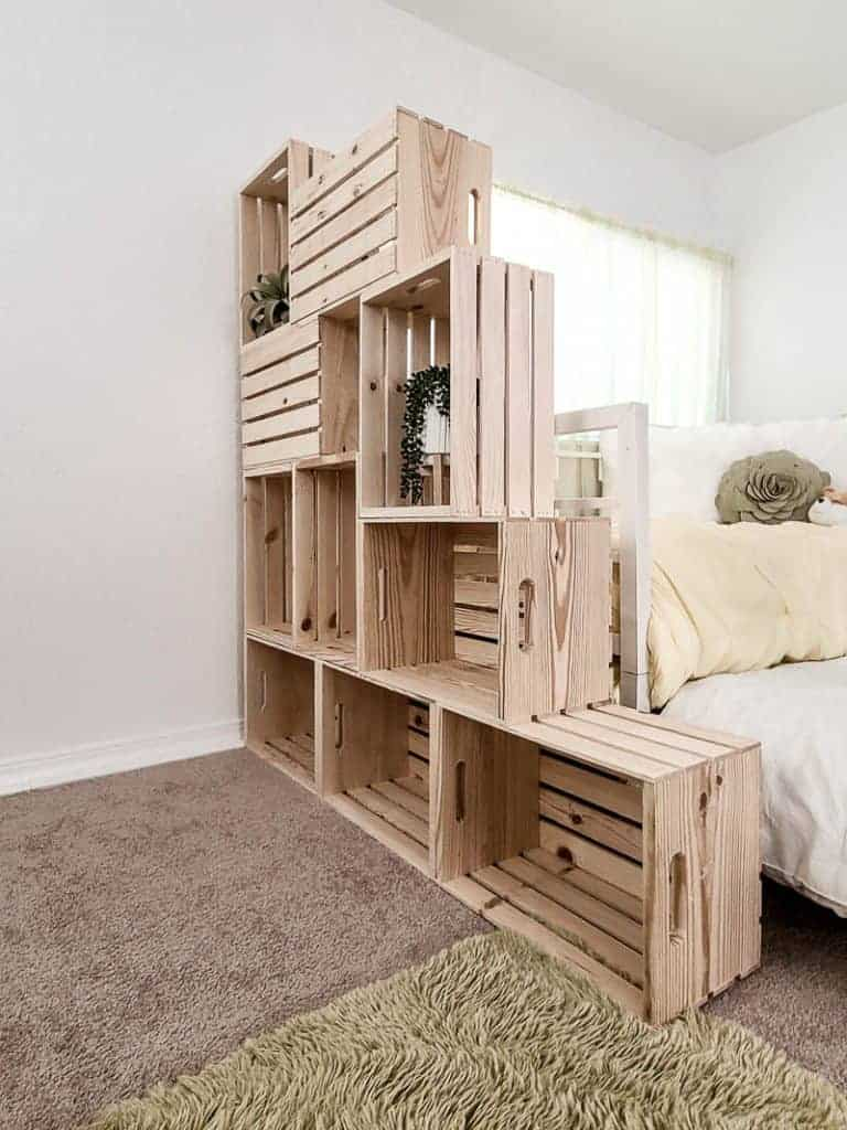 shows a side view of the wood crate bookshelf by a bed and with plants in it