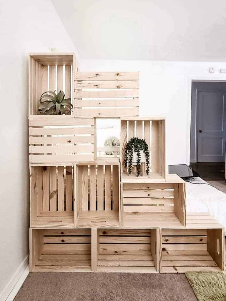 shows 10 wood crate stacked on each other to create a wall with some plants in it