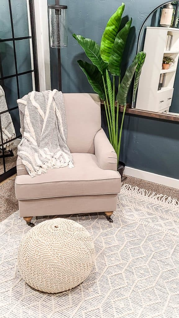 shows a corner of the dark teal office with a cream linen arm chair and faux plant, arch mirror on shelf and white boho rug