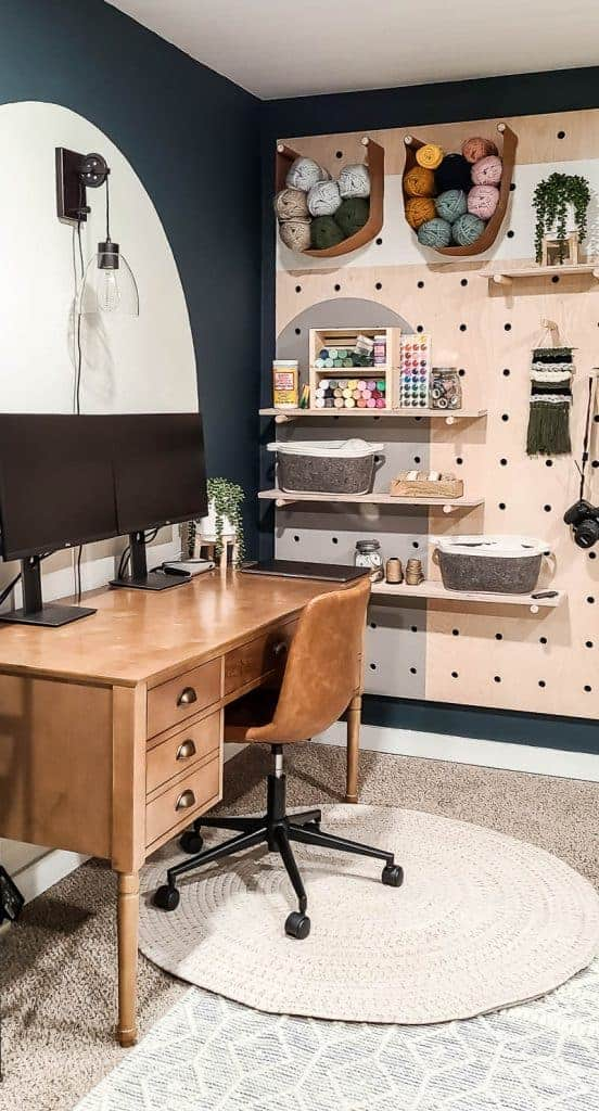 shows the giant wood pegboard with craft supplies next to a wood desk with a leather chair on a white rug with a white backdrop and dark teal walls