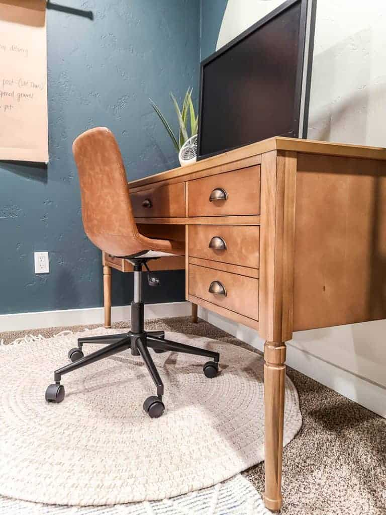 shows a wood desk with vintage brass pulls with a leather chair and white round rug