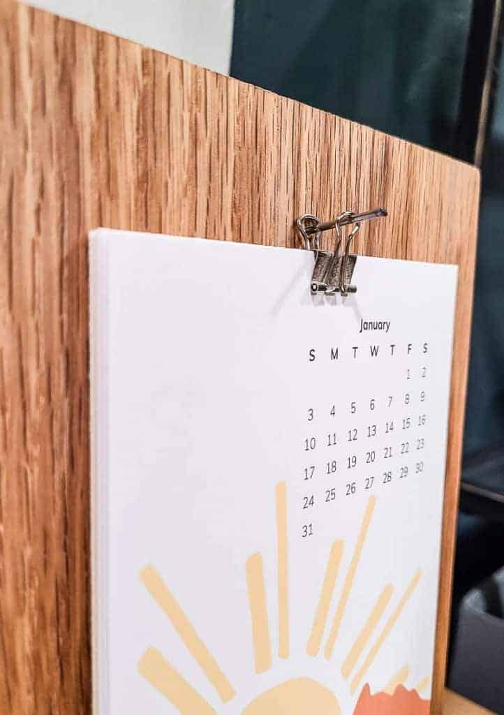 shows and up close picture of the desk calendar hanging on a binder clip
