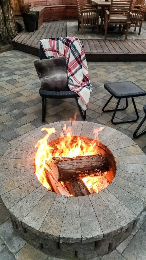 shows the paver fire pit with logs on fire