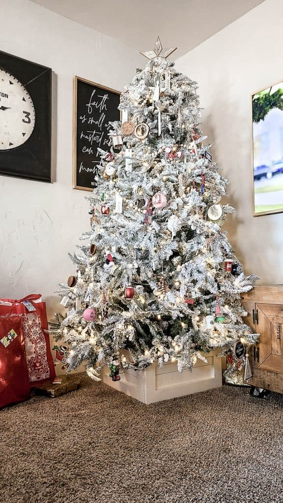 shows the Christmas tree with the wooden box stand made with shiplap with farmhouse style decorations
