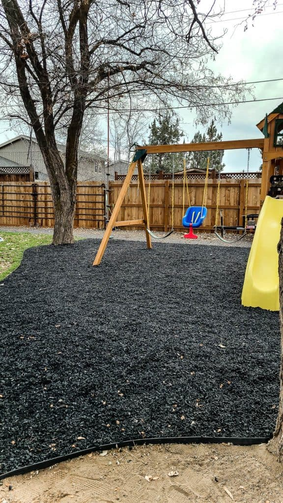 shows part of a kids swing set in a backyard with black rubber mulch with fence in background