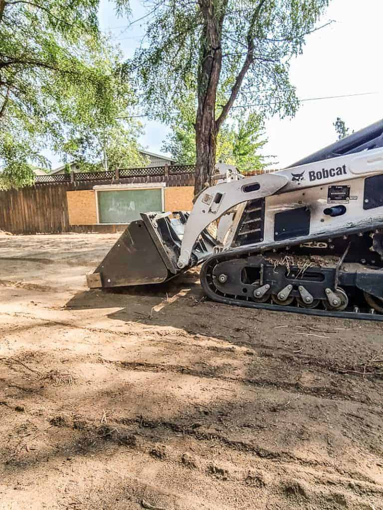 shows a bobcat skid steer leveling out dirt in backyard for renovation