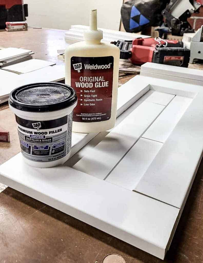 shows Weldwood glue, wood filler and shiplap on a workbench in garage