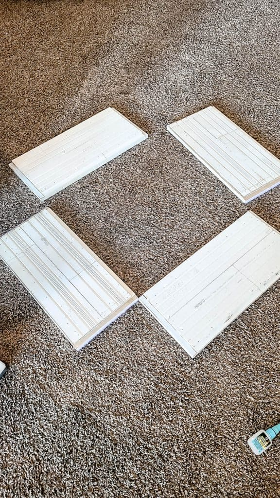 shows the shiplap tree stand pieces laying on the ground to show that they store flat