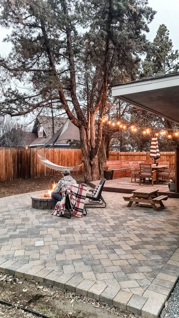 man sits in front of lit fire pit on paver patio