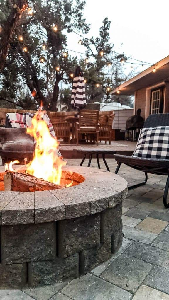 shows paver fire pit with new deck in background