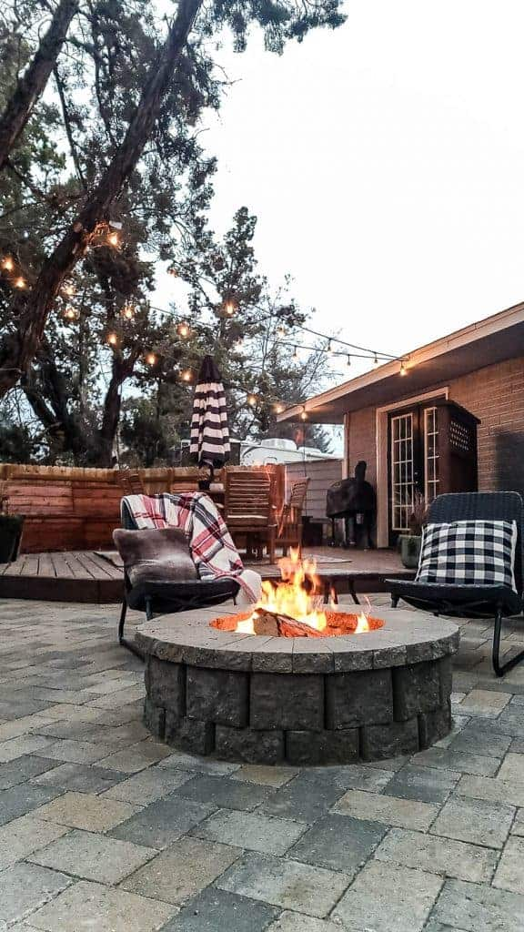 photo set in the evening, fire pit is lit, string lights in the background are on