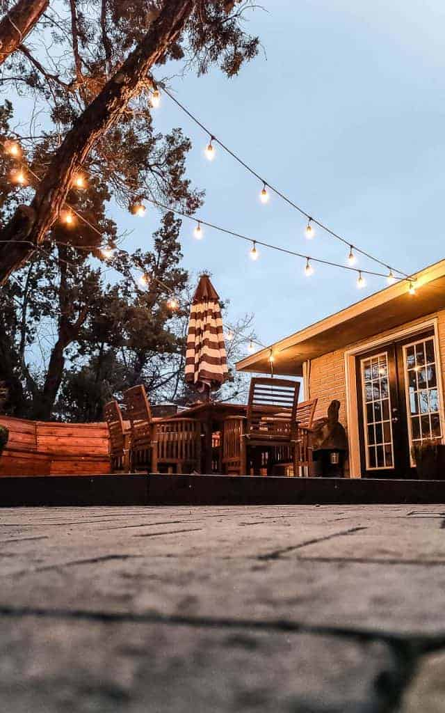 shows a view of the wood stained deck under edison bulb string lights in backyard with wooden table and striped umbrella