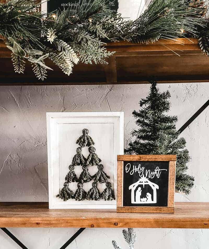 Christmas tree tassel art on shelf with small Christmas tree and O Holy Night frame