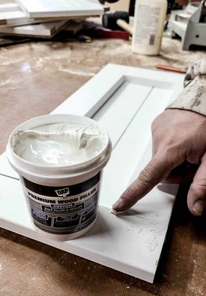 shows wood filler being applied with finger to nail holes