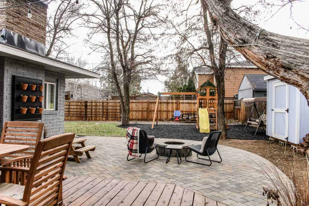 shows paver patio and fire pit with chairs and swing set in backyard with fence and grass shown in background
