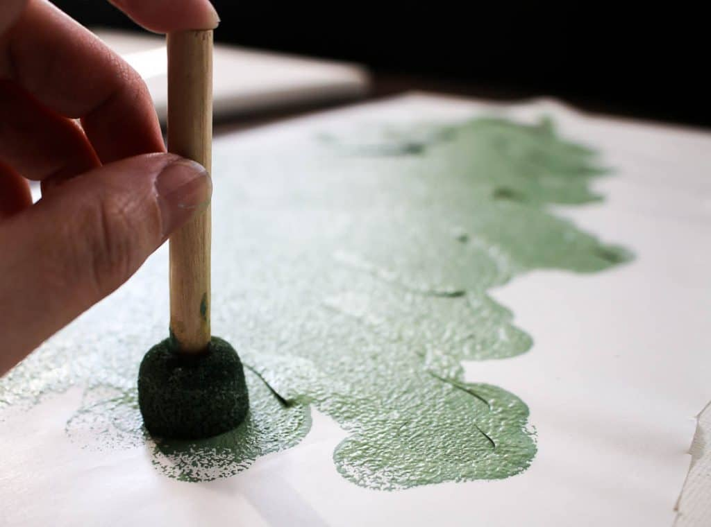 shows a hand painting a tree on a canvas with stencil