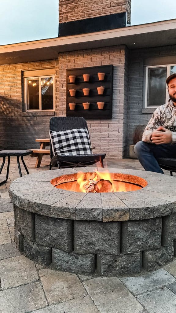 shows the fire pit being used in renovated backyard