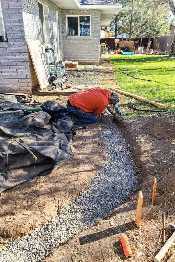 a man arranges edge pavers along the patio space in a gravel trench for border