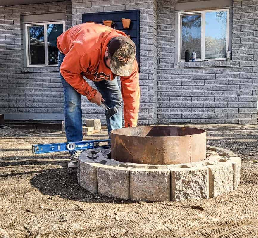 shows a man leveling out pavers