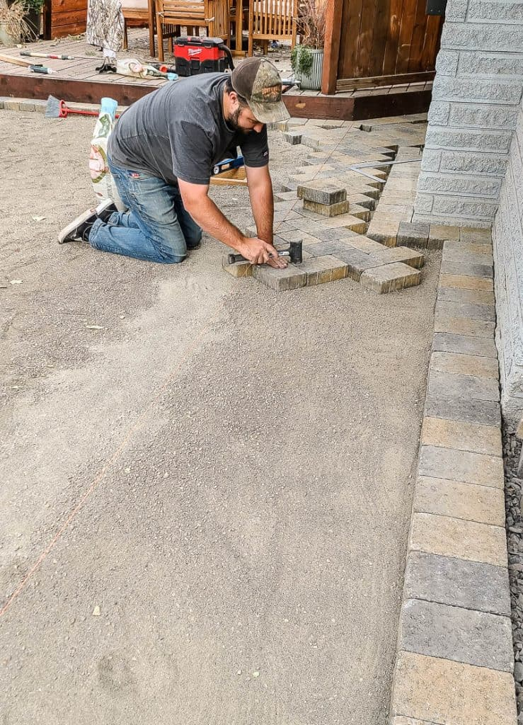 Man lays pavers in a row along one edge in a herringbone pattern