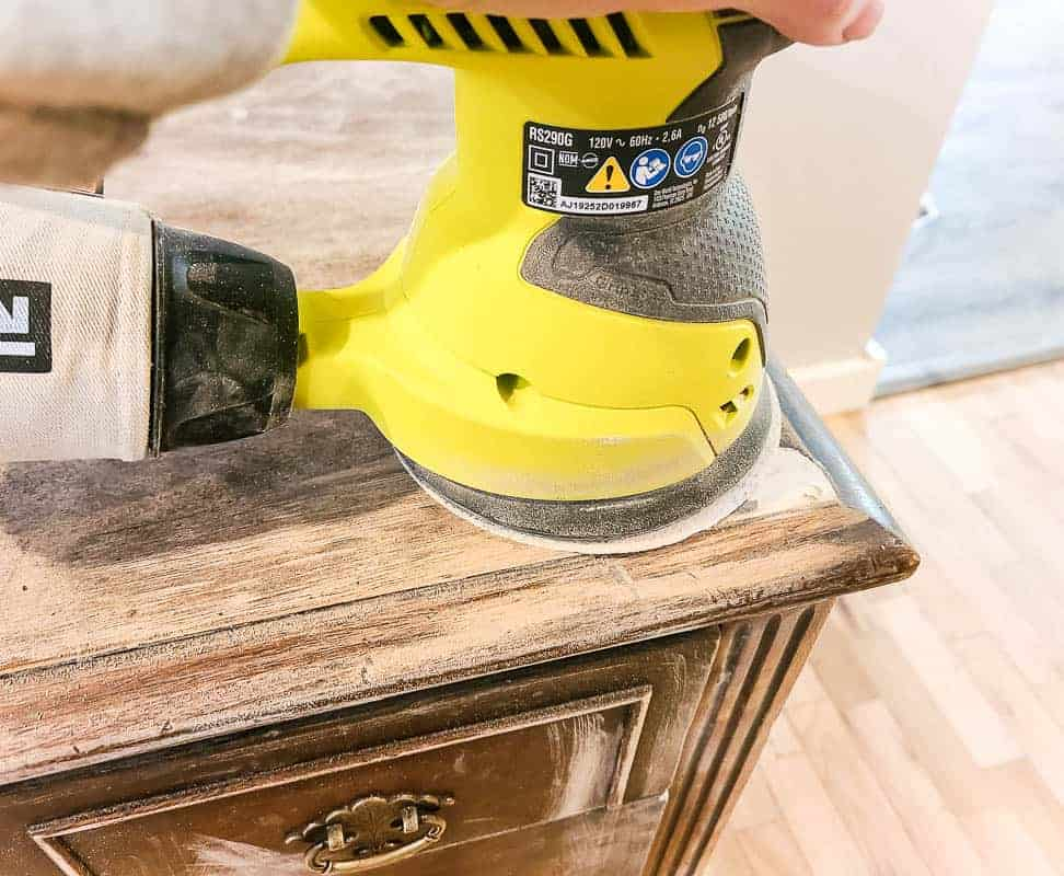 shows an orbital sander sanding the putty on the corner of a wood desk