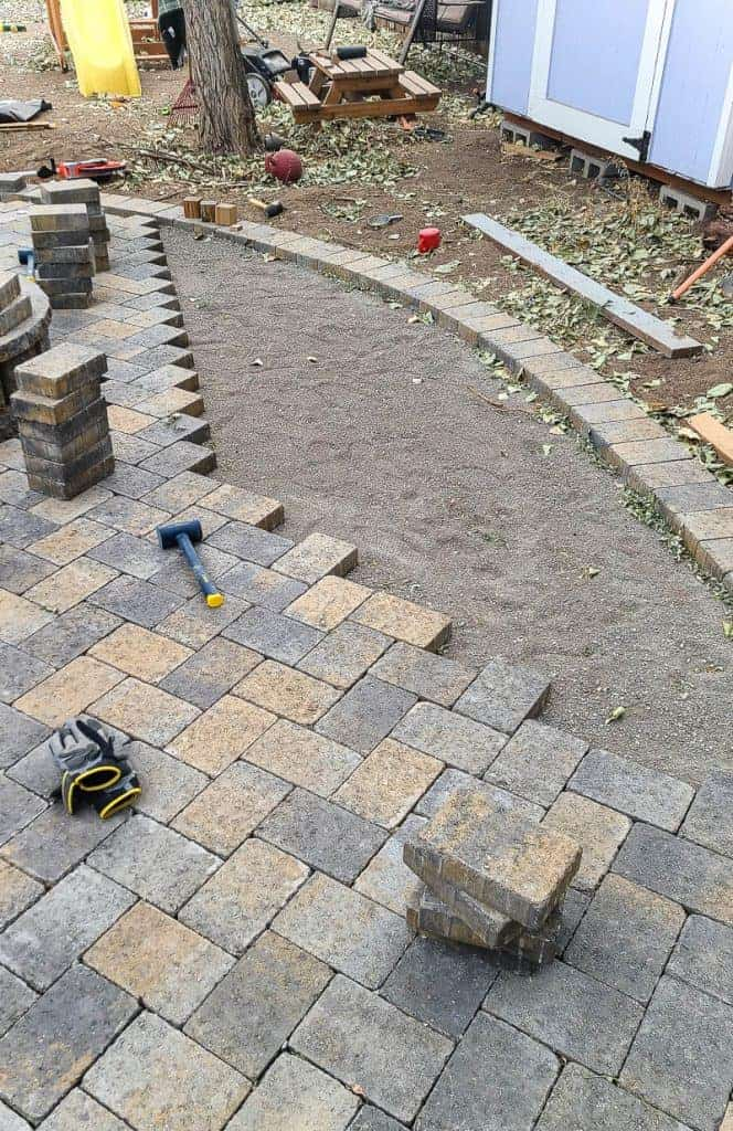 pavers are laid out for a patio, stacks of pavers and a mallet sit on the pavers that are in place