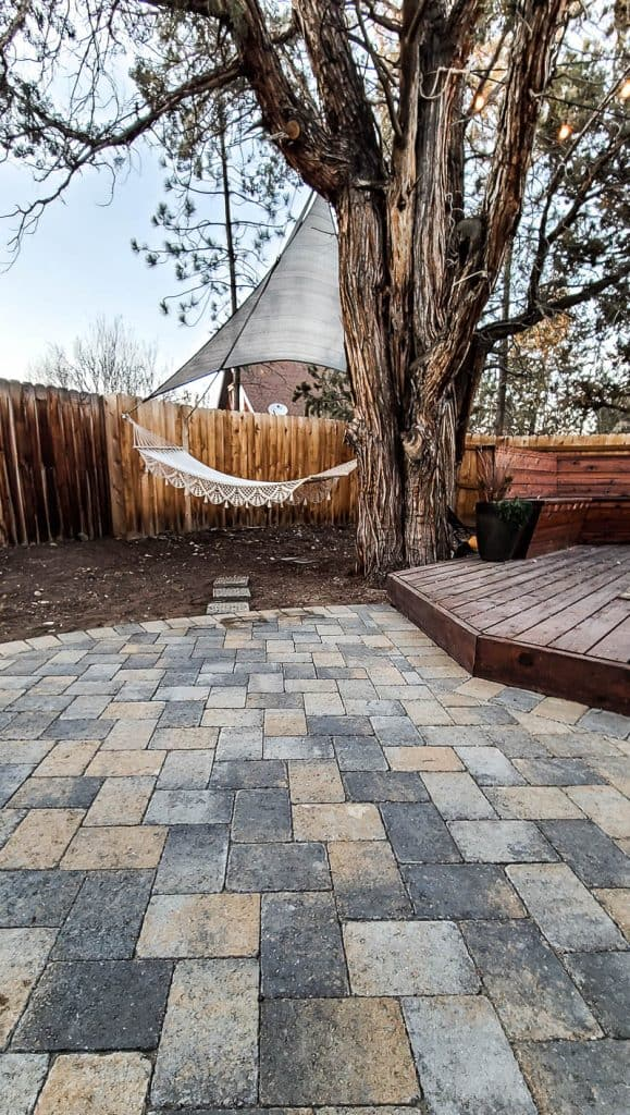 herringbone pattern paver patio with macrame hammock and wood deck in the background