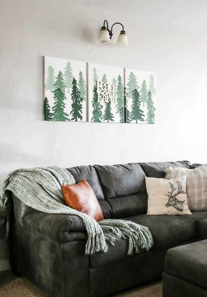 3 Christmas tree canvases hanging over a gray couch