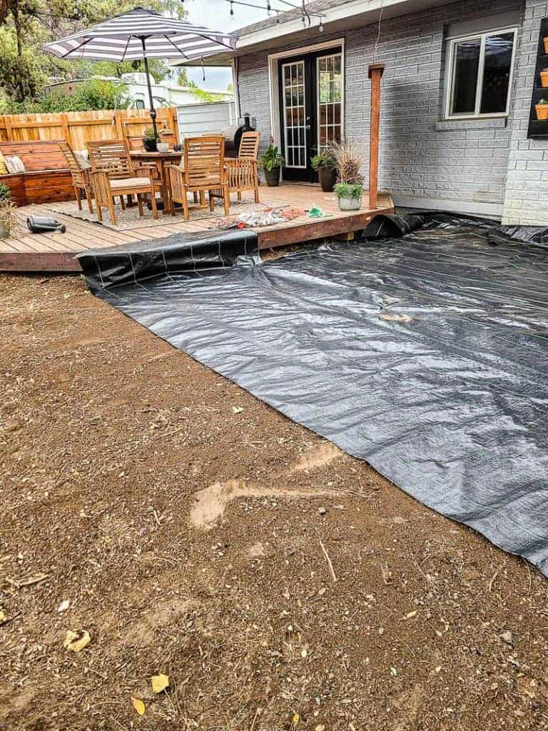 Landscape fabric is laid across the ground under paver patio area before installing