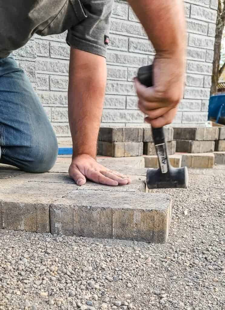 Man hammers pavers to be flush with each other