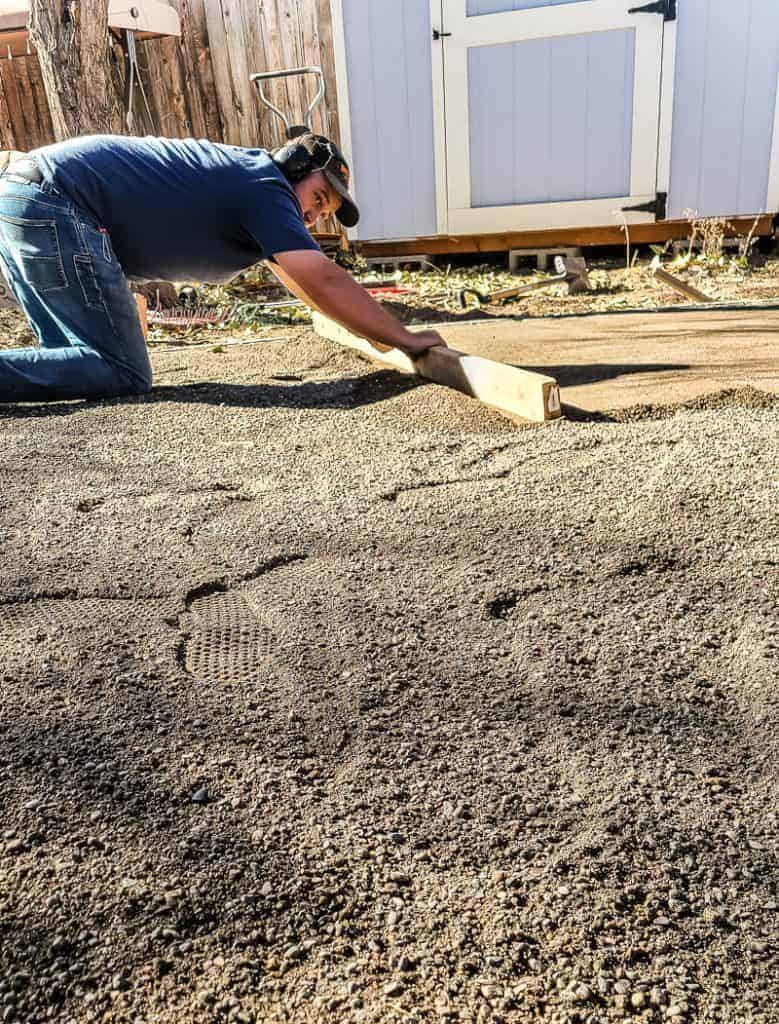 man uses two by four to level the paver base sand before adding a DIY paver patio with fire pit