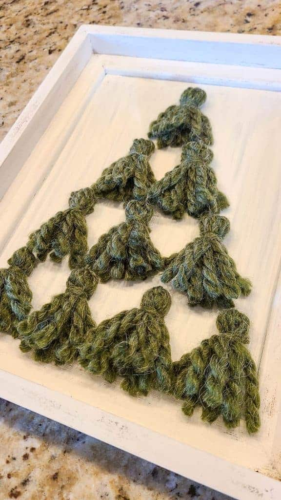 White frame with green yarn tassels in shape of Christmas tree