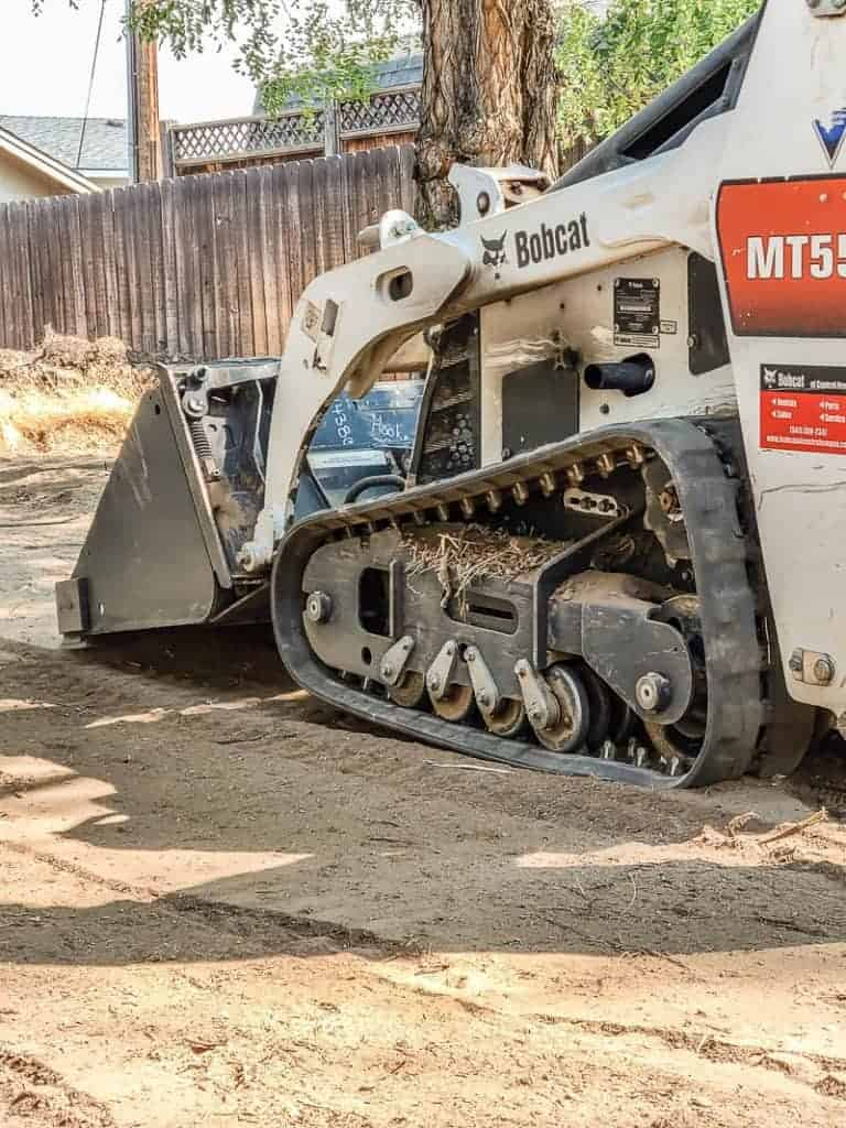 a bobcat tractor is flattening the dirt in backyard