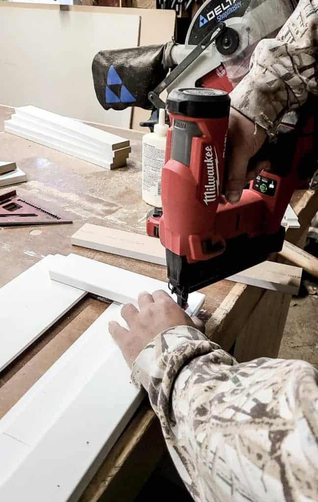 shows a man using a brad nailer to put the nails into the box
