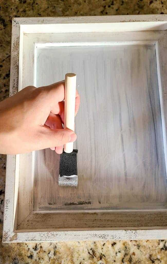 Painting a sign white with sponge brush